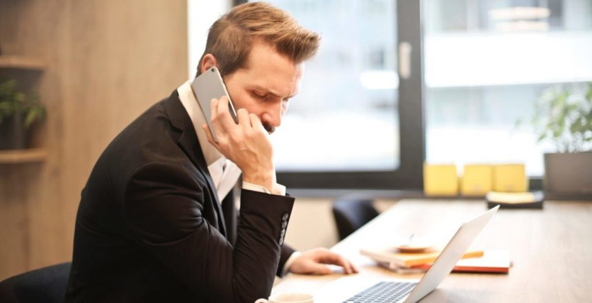 man-having-a-phone-call-in-front-of-a-laptop-859264